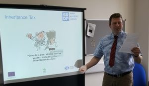 Person giving a presentation with a screen behind him