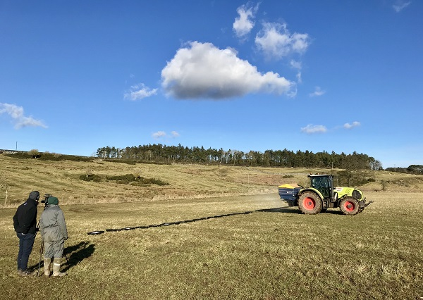 Field showing a fertiliser sower on the back of a Claas tractor. There are two men standing watching the fertiliser being sown during a fertiliser spreader calibration assessment