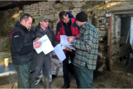 Farmers at the Knockglass Soil & Nutrient Network meeting at Knockglass Farm, Caithness. They are all looking through handouts from the event