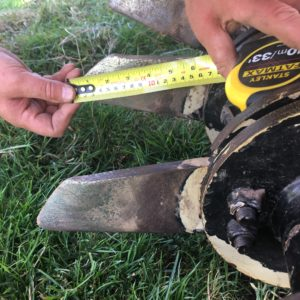A photo of someone measuring the length of blade on a soil aerator with a yellow measuring tape