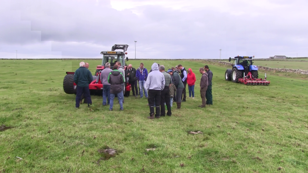 Farmers attending the Orkney SNN meeting standing in a grassland field with soil compaction remediation machinery
