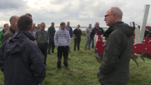 Group of farmers in a field with a sward lifter during the Orkney SNN meeting