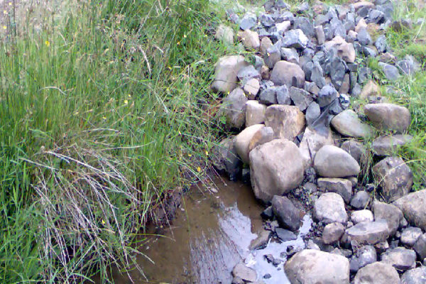 A water extraction point in a watercourse. There are a lot of river stones that can be seen from which the watercourse appears from. The abstraction point is below the river stones.