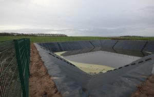 Slurry lagoon with safety fence