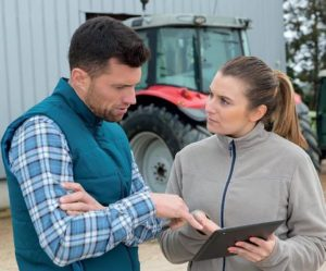 Two farmers discussing list on clipboard, tractor in background