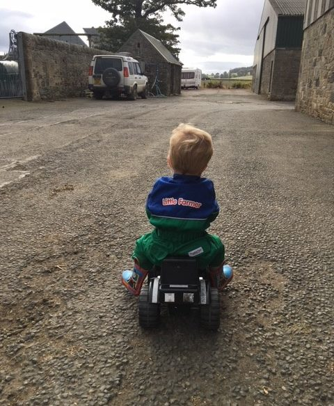 Small child riding a toy tractor wearing a boilersuit with the words ' Little Farmer' on it