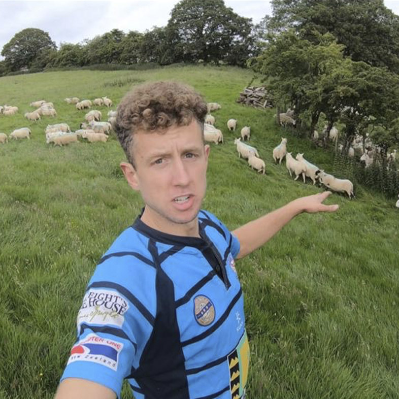 Young Farmer in a field of sheep, pointing at the sheep.