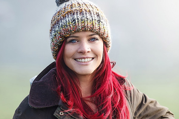 Hannah Jackson, The Red Shepherdess, Smiling in a field.